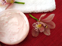 Container of cosmetic moisturizing cream with pink orchids with Royalty Free Stock Photo