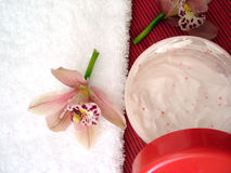 Container of cosmetic moisturizing cream with pink orchids and t. Owel Stock Image