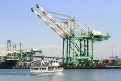 Container crane at Los Angeles harbor. A giant container crane loans over the busy port of Los Angeles as a tourist boat passes by Stock Photo