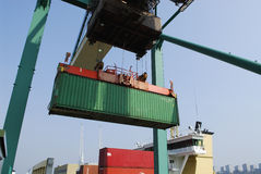 Container, crane and ship. Container transported in air infront of ship Royalty Free Stock Photo