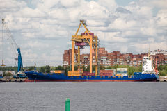 Container crane unloads container ship in Moby Dik terminal, Kronshtadt, Russia Royalty Free Stock Photos