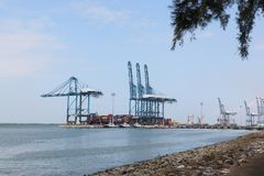 Container cranes at works, North Port, Port Klang, Malaysia. Port Klang, Malaysia - December 13, 2017 : Cranes unloading containers at Kelang Container Terminal Royalty Free Stock Photos