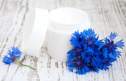 Container with cream  and cornflowers Stock Images
