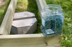 Container of deck screws, deck block and frame. Container of deck screws sitting on an unfinished frame with a deck block in the background Royalty Free Stock Photos