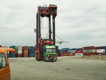 Straddle carrier loading a container stock photography