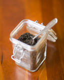 Container of dried tea. Glass container filled with loose leaf black tea Royalty Free Stock Photos