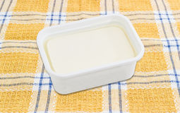 Container of feta cheese on a checkered tablecloth Stock Image