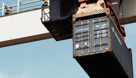 Container on giant crane. Container on docks ready to be charged on truck Stock Photos