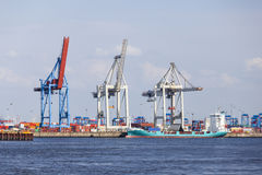 Container Harbor in Hamburg, Germany. Container harbor with tall cranes and docked ship in Hamburg Harbor, Germany Stock Images
