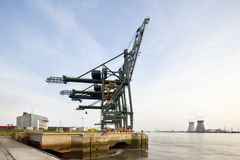 Container Harbor And Power Station. A container terminal with tall cranes with a nuclear power station in the background. Shot taken in Antwerp, Belgium Royalty Free Stock Photography