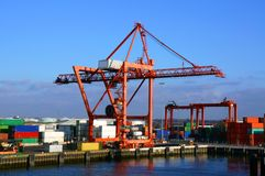 Container Loading Crane, Dublin Port. A large red container loading crane surrounded by stacks of different colored containers on the quayside at Dublin Port Royalty Free Stock Images