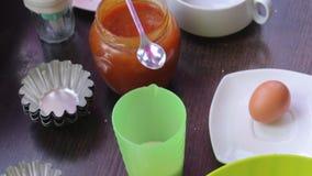 Container met gesmolten boter en andere ingrediënten voor het koken van cakes Vormen voor bakselcakes Tribune op de lijst stock footage