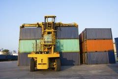 Container met vorkheftruck op blauwe hemel Stock Afbeelding