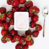 Container met yoghurt en een stapel van verse aardbeien op wit Royalty-vrije Stock Foto's