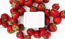 Container met yoghurt en een stapel van verse aardbeien op wit Stock Fotografie
