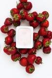 Container met yoghurt en een stapel van verse aardbeien op wit Stock Foto