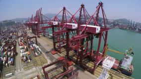 Container Port Crane 4K Aerial Shot. 4K aerial shot of a container terminal. Slightly track left shot. With crane loading cargos to container vessel and trucks stock footage