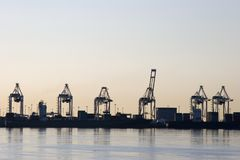 Container Port Cranes. A row of container port cranes silhouetted against an evening sky Stock Image