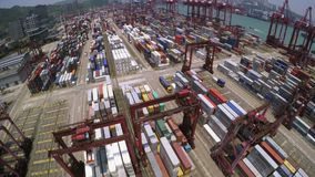 Container Port. 4K Aerial Shot. 4K aerial shot of a container terminal. Tilt up from containers to the whole terminal area. With crane loading cargos to stock video footage