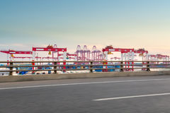 Container port with road at dusk. Road motion blur with modern container port at dusk Royalty Free Stock Photo