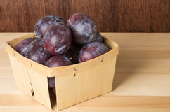 Container of prune plums on table Royalty Free Stock Images
