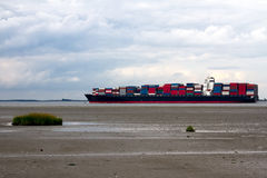 Container ship. A container ship leaving an estuary Stock Photography