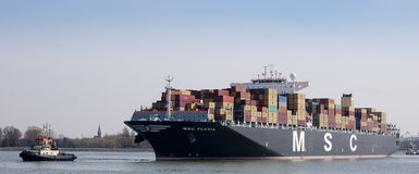 Container ship. Msc flavia one of the largest container-ships in the world, guided by a tug into the Berendrechtsluis, the largest dock of the world, port of Royalty Free Stock Photo