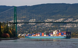 Container Ship. Large container ship is passing under the Lions Gate Bridge in Vancouver, Canada stock image