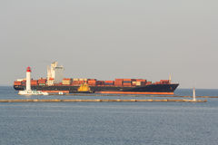 Container ship with accompanying tugboats entering the port Royalty Free Stock Photo