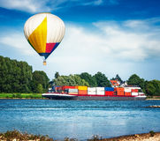 Container ship and air hot balloon. Container ship on the river. Air hot balloon floating over summer landscape royalty free stock photography