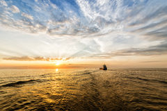 Container ship alonge the waterway. Amaizing Sunset. Empty container ship is sailing alonge the waterway during sunset. Small ship, colorfull sky and sea Royalty Free Stock Image