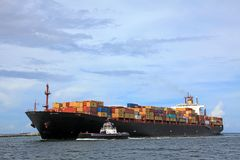 A container ship carrying colorful containers. A tugboat assists a container ship as it heads out to sea carrying colorful containers Stock Photography