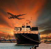Container ship and container in shipping port cargo plane flying above Stock Image