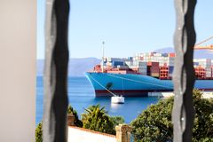 Container ship with containers to shore in port ship port on horizon / Cargo transportation by sea and goods unloading process. Container ship for carriage of Stock Photography