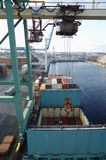 Container ship, crane and port. Crane lowering containers into ship in a commercial port, elevated view from above Stock Photo