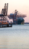 Container Ship and Cranes. A large container ship unloads its cargo at a large industrial shipyard and dock facility Stock Image