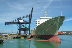 Container ship at dock. Empty container ship at dock next to black dock cranes Royalty Free Stock Photography