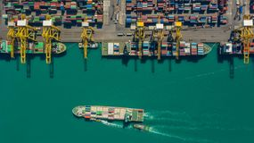 Container ship in export and import business logistics and transportation. Cargo and container box shipping to harbor by crane. stock photos