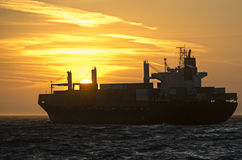 Container ship in front of sunset Royalty Free Stock Images