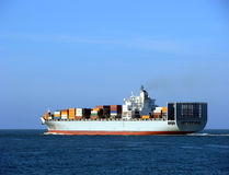 Container Ship with Full Load Sailing Away at Sea. Loaded ocean going container ship vessel sailing away at sea Royalty Free Stock Photos