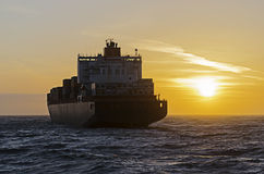 Container ship heading towards sunset Royalty Free Stock Photos