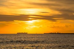 Container ship on the horizon at sunset stock photography