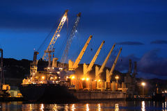 Container ship in la spezia harbor by night. Illuminated container ship under large cranes at twilight in la spezia Harbor Royalty Free Stock Image