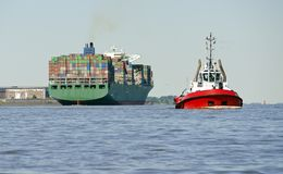 Container ship and harbour tow boat royalty free stock photography