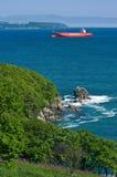 Container ship Monte Sarmiento runs along the green coast. Nakhodka Bay. East (Japan) Sea. 27.05.2014 Royalty Free Stock Images