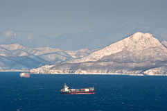 Container ship moving by sea along the coast of the mountainous winter. Nakhodka Bay. East (Japan) Sea. 02.01.2013 Stock Images