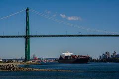 The container ship passes under the bridge. Logistics and transportation of International Container Cargo ship in the ocean, Nautical Vessel Royalty Free Stock Photos