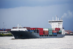 Container ship in port. Navigating river under storm skies Royalty Free Stock Images