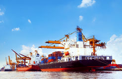 Container ship in port cargo dock with piers crane tool use for Stock Photo