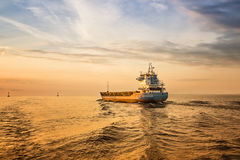 Container Ship on Sea Road during Sunset. Amaizing Sunset. Empty container ship is sailing alonge the waterway during sunset. Small ship, colorfull sky and sea Stock Images